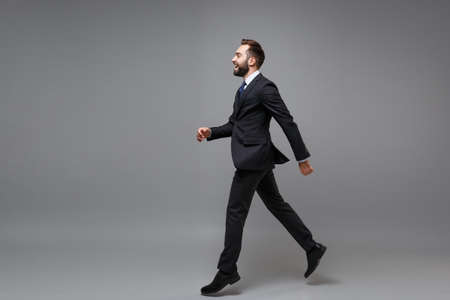 Foto de Side view of laughing young business man in classic suit shirt tie posing isolated on grey background. Achievement career wealth business concept. Mock up copy space. Running, jumping, looking aside. - Imagen libre de derechos