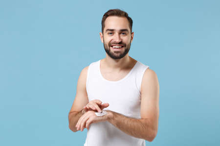 Photo pour Bearded young man 20s years old applying moisturizer facial cream from container isolated on blue pastel background studio portrait. Skin care healthcare cosmetic procedures concept Mock up copy space - image libre de droit