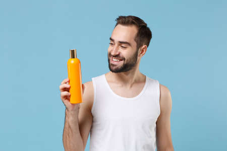 Photo pour Bearded young man 20s years old in white shirt hold bottle of shampoo isolated on blue pastel wall background, studio portrait. Skin care healthcare cosmetic procedures concept. Mock up copy space. - image libre de droit