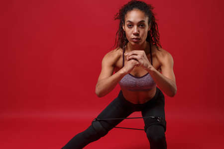 Photo pour Beautiful young african american sports fitness woman in sportswear working out isolated on red background. Sport exercises healthy lifestyle concept. Stretching legs, doing lunges with elastic band. - image libre de droit