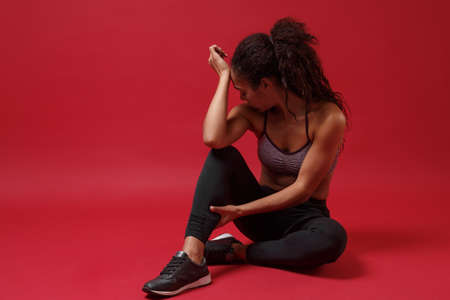 Photo for Dissatisfied young african american sports fitness woman in sportswear posing working out isolated on red background. Sport exercises healthy lifestyle concept. Sit, touching ankle, put hand on head. - Royalty Free Image
