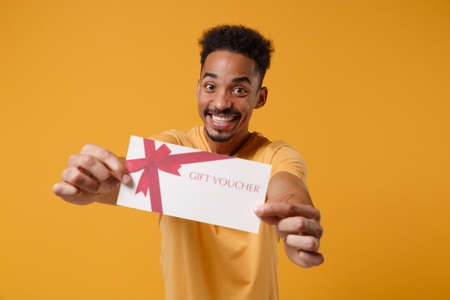 Photo pour Cheerful young african american guy in casual t-shirt posing isolated on yellow orange background studio portrait. People sincere emotions lifestyle concept. Mock up copy space. Hold gift certificate. - image libre de droit