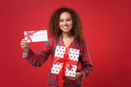 Photo pour Joyful african american girl in pajamas homewear rest at home isolated on red background. Relax good mood lifestyle concept. Mock up copy space. Hold present box with gift ribbon bow gift certificate. - image libre de droit