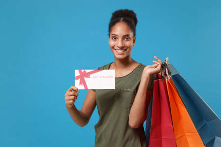 Photo pour Joyful young african american woman girl in casual t-shirt isolated on blue background. People lifestyle concept. Mock up copy space. Hold package bag with purchases after shopping, gift certificate. - image libre de droit