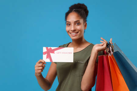 Photo pour Smiling young african american woman girl in casual t-shirt isolated on blue background. People lifestyle concept. Mock up copy space. Hold package bag with purchases after shopping, gift certificate. - image libre de droit