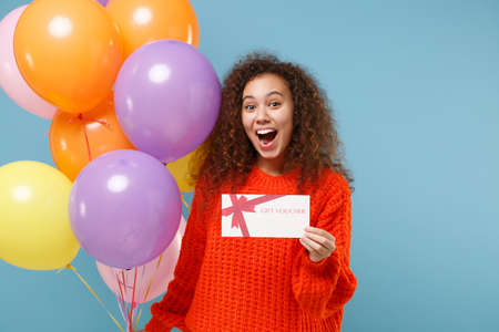 Photo pour Excited young african american girl in casual orange knitted clothes isolated on pastel blue wall background. Birthday holiday party concept. Celebrating holding colorful air balloon gift certificate. - image libre de droit