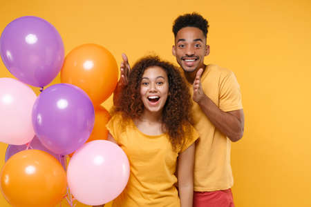 Photo pour Surprised young friends couple african american guy girl in casual clothes isolated on yellow orange background. Birthday holiday party people emotions concept. Celebrating hold colorful air balloons. - image libre de droit