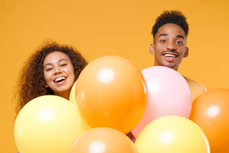 Photo pour Laughing young friends couple african american guy girl in casual clothes isolated on yellow orange background. Birthday holiday party, people emotions concept. Celebrating hold colorful air balloons. - image libre de droit
