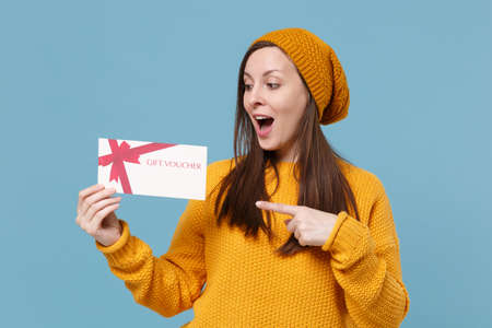 Photo pour Excited young woman in yellow sweater hat posing isolated on blue background studio portrait. People sincere emotions lifestyle concept. Mock up copy space. Pointing index finger on gift certificate. - image libre de droit