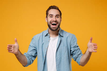 Photo pour Excited young bearded man in casual blue shirt posing isolated on yellow orange wall background. People lifestyle concept. Mock up copy space. Gesturing demonstrating size with horizontal workspace. - image libre de droit