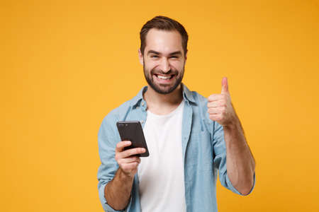 Photo pour Smiling young man in casual blue shirt posing isolated on yellow orange wall background in studio. People lifestyle concept. Mock up copy space. Using mobile phone typing sms message showing thumb up. - image libre de droit