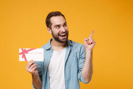 Photo pour Cheerful young man in casual blue shirt posing isolated on yellow orange wall background, studio portrait. People lifestyle concept. Mock up copy space. Hold gift certificate pointing index finger up. - image libre de droit