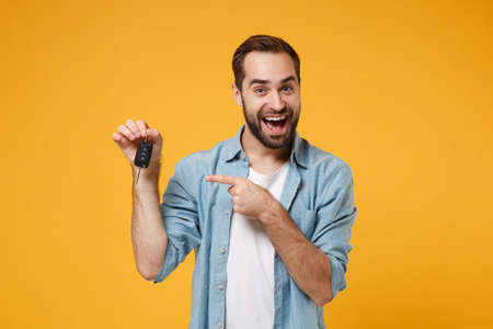 Photo pour Excited young man in casual blue shirt posing isolated on yellow orange background, studio portrait. People sincere emotions lifestyle concept. Mock up copy space. Pointing index finger on car keys. - image libre de droit
