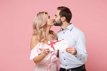 Photo pour Young couple two guy girl in party outfit celebrating posing isolated on pastel pink background. People lifestyle Valentines Day, Womens Day birthday holiday concept. Hold gift certificate, kissing. - image libre de droit