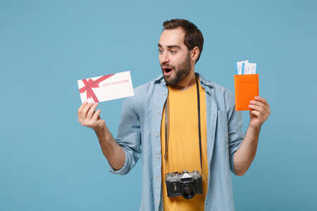 Photo pour Surprised traveler tourist man in summer clothes with photo camera isolated on blue background. Passenger traveling on weekends. Air flight journey Hold passport boarding pass ticket gift certificate. - image libre de droit