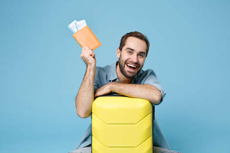 Photo pour Funny traveler tourist man in yellow clothes isolated on blue background. Passenger traveling abroad on weekend. Air flight journey concept. Sitting near suitcase hold passport boarding pass tickets. - image libre de droit