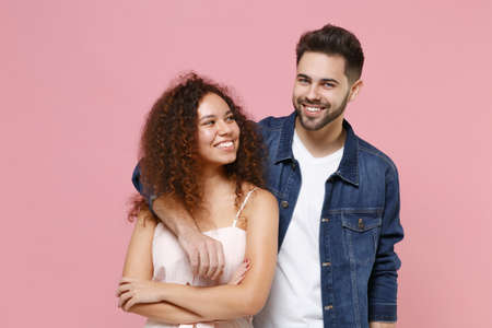 Foto de Smiling young couple two friends european guy african american girl in casual clothes isolated on pastel pink background. People lifestyle concept. Mock up copy space. Hugging, looking at each other. - Imagen libre de derechos