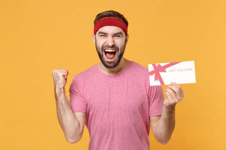 Photo pour Screaming bearded fitness sporty guy sportsman in headband t-shirt in home gym isolated on yellow background. Workout sport motivation lifestyle concept. Hold gift certificate, doing winner gesture. - image libre de droit