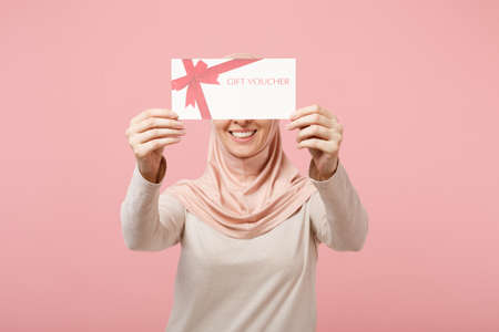Photo pour Smiling young arabian muslim woman in hijab light clothes posing isolated on pink background in studio. People religious Islam lifestyle concept. Mock up copy space. Holding in hands gift certificate. - image libre de droit