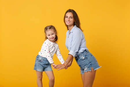 Foto de Woman in light clothes have fun with cute child baby girl 4-5 years old. Mommy little kid daughter isolated on yellow background studio portrait. Mothers Day love family parenthood childhood concept. - Imagen libre de derechos
