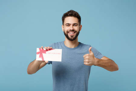 Photo pour Young smiling man in casual clothes posing isolated on blue wall background, studio portrait. People sincere emotions lifestyle concept. Mock up copy space. Holding gift certificate, showing thumb up. - image libre de droit