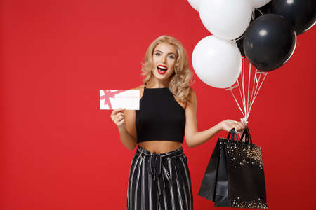 Photo pour Cheerful young woman girl in black clothes posing isolated on red wall background. Shopping discount sale concept. Mock up copy space. Holding air balloons package bag with purchases gift certificate. - image libre de droit
