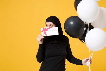 Photo pour Arabian muslim woman in hijab celebrating hold voucher black white air balloons isolated on yellow background studio portrait. Birthday holiday people religious lifestyle concept. Mock up copy space. - image libre de droit