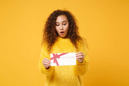 Photo pour Shocked young african american girl in fur sweater posing isolated on yellow orange background studio portrait. People lifestyle concept. Mock up copy space. Hold gift certificate, keeping mouth open. - image libre de droit