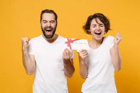 Photo pour Joyful couple friends bearded guy girl in white blank empty t-shirts isolated on yellow orange background. - image libre de droit