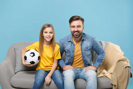 Smiling bearded man with cute child baby girl. Father little kid daughter isolated on pastel blue background. Love family parenthood childhood concept. Cheer up support favorite team with soccer ball.