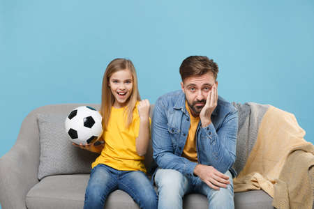 Funny man with cute child baby girl. Father little daughter isolated on blue background. Love family parenthood childhood concept. Cheer up support favorite team with soccer ball doing winner gesture.