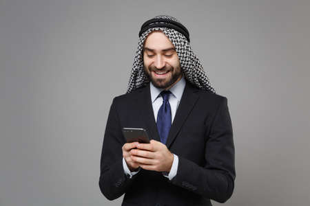 Photo pour Smiling arabian muslim businessman in keffiyeh kafiya ring igal agal classic black suit isolated on gray background. Achievement career wealth business concept. Using mobile phone, typing sms message. - image libre de droit
