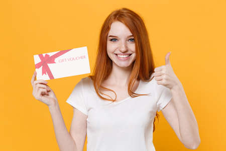 Photo pour Smiling young redhead woman girl in white blank empty t-shirt posing isolated on yellow wall background in studio. People lifestyle concept. Mock up copy space. Hold gift certificate showing thumb up. - image libre de droit
