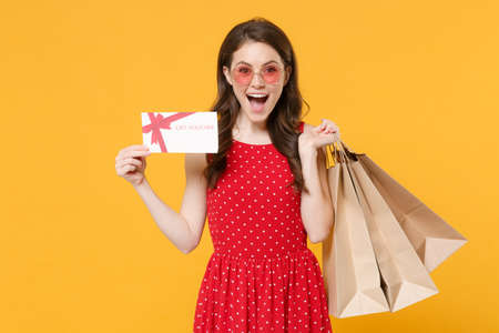 Photo pour Excited young brunette woman girl in red summer dress eyeglasses posing isolated on yellow background studio. People lifestyle concept. Hold package bag with purchases after shopping gift certificate. - image libre de droit