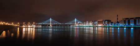 Panorama of the night city. Night lights of St. Petersburg. View of the big Obukhov bridge with a backlight across the river