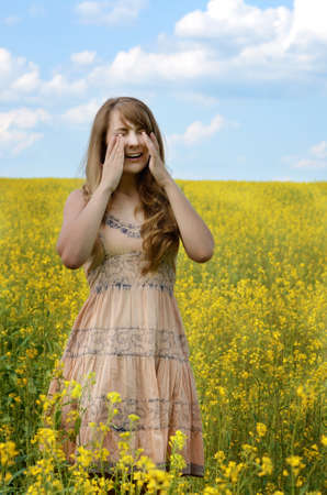 Young woman sneezing at canola field suffering from hay fever or allergy