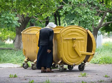 Makeevka, Ukraine - May 29, 2015: An elderly woman near a garbage bin