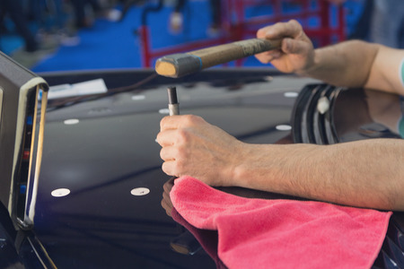 Photo pour Hands of the master during the work on the straightening of the car's hood. Industry - image libre de droit