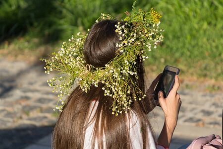 Girl in a wreath from herbs with the smartphone. National Slavic holiday of Ivan Kupala