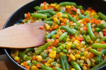 Photo pour Colorful mix of vegetables is fried in a frying pan close up. Food - image libre de droit