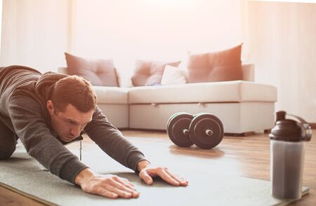 Photo pour Young ordinary man go in for sport at home. Cut view of beginner guy stretching his body and pull hands foward on mat. Improving body shape. Real man with no knowledge in sport start workout. - image libre de droit
