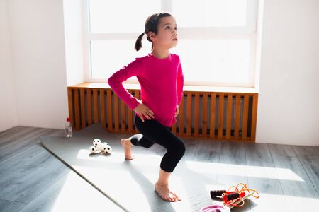 Photo pour Little girl forward lunge workout at home. Cute kid is training on a mat indoor. Little dark-haired female model in sportswear has exercises near the window in her room - image libre de droit