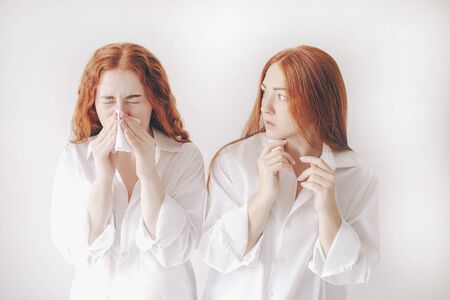 young woman with handkerchief. Sick girl has runny nose. Female model makes a cure for the common cold isolated on white background background. The second young woman is afraid to get infected