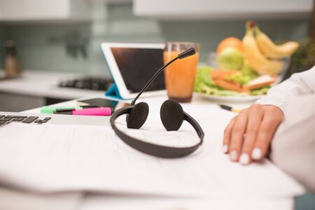 Photo for headphones with a headset are on the table. Close-up workplace in the kitchen. A woman works from home. There is a laptop, pen, tablet, pencil, notebook, markers - Royalty Free Image