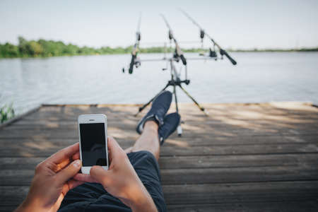 Photo pour Young fisherman fishing on lake or river. A view of guy's eyes sitting on pier and using smartphone. Waiting for catching some fish. Guy using three fishing rods for water hunting. Beautiful sunny day - image libre de droit