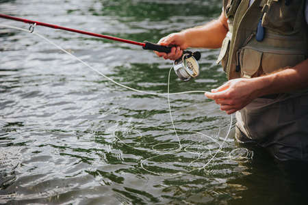 Young fisherman fishing on lake or river. Cut view of guy's hands holding fishing line. Preparing to catch some river or lake fish. Man stand in fresh water