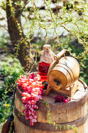 Old wooden wine barrel with bottle of wine and grapes on it. Wedding decorations outdoors
