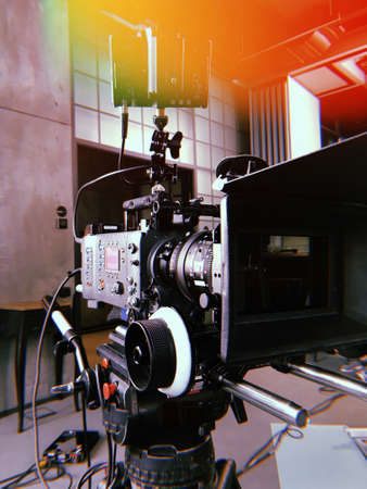 movie camera on the tripod, interior set