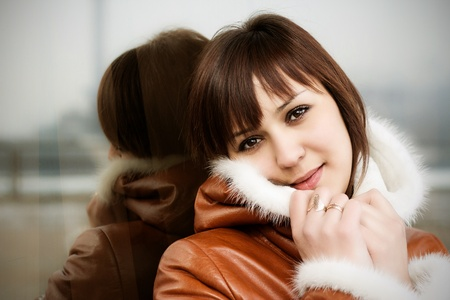 beautiful girl with brown eyes, walking on the street in winter