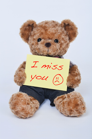 Foto für A cute teddy bear holding a yellow sign that says I miss you isolated on a white background - Lizenzfreies Bild